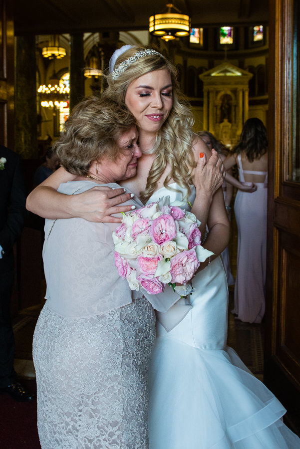 bride hugging crying grandmother after ceremony in church