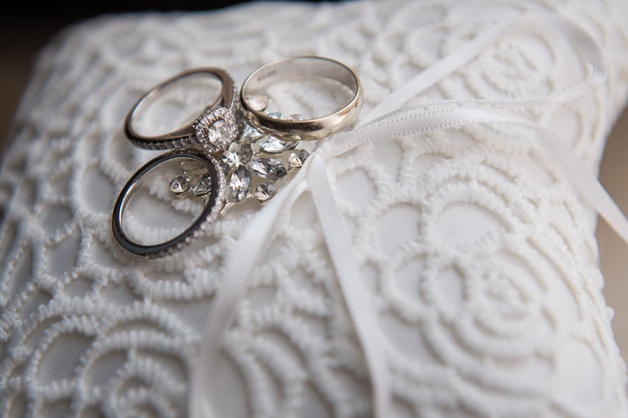 detail close up photo of wedding rings and engagement ring