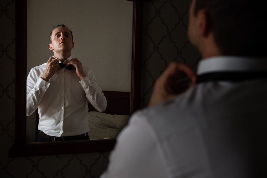 groom looking at mirror fixing bow tie
