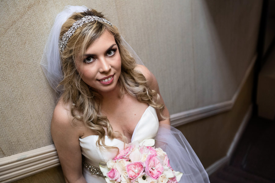 bridal portrait with sky light holding flowers on the stairs