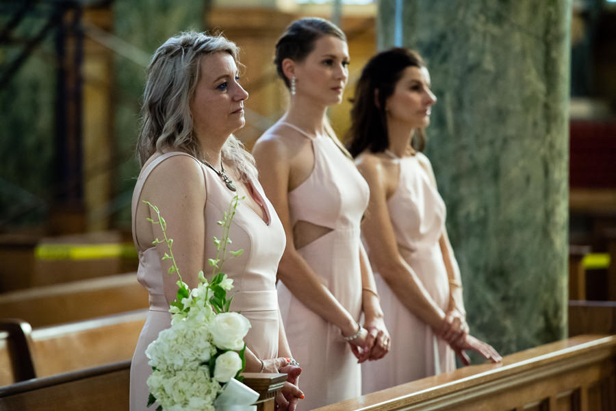 bridesmaids standing in church during ceremony