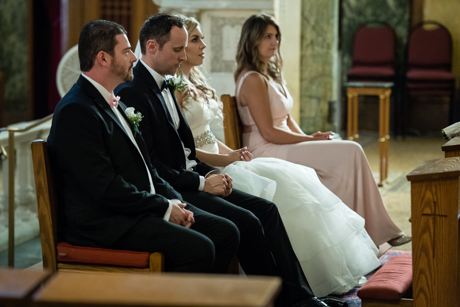 wedding couple sitting in church with best man and maid of honor