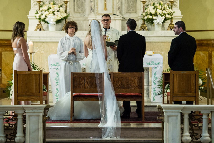 bride and groom standing in church at the ceremony in St. Matthias Church in Ridgewood NY