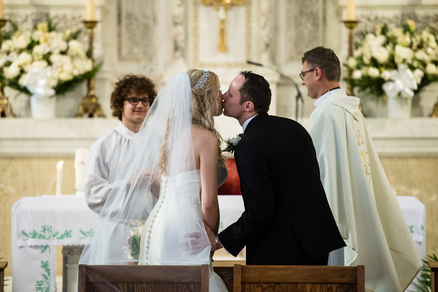 Bride and groom kissing at the alter in St. Matthias Church in Ridgewood NY