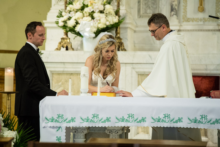 bride and groom signing contract in st bride and groom walking down aisle in St. Matthias Church in Ridgewood NY