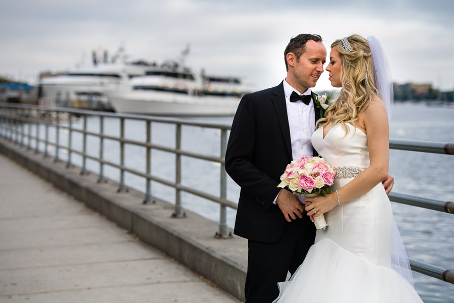 bride and groom photo session in sheepshead bay with yachts in the background by the water