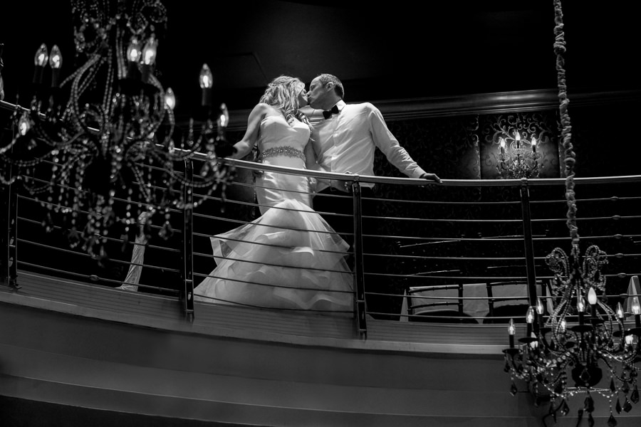 bride and groom kissing on balcony in romanoff restaurant with beautiful chandeliers