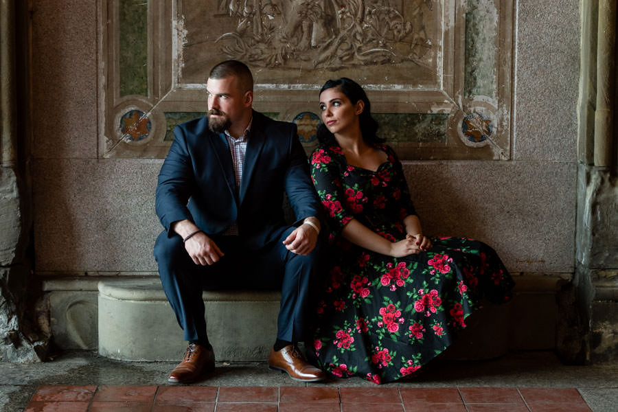 couple sitting under bethesda terrace during their engagement session in central park
