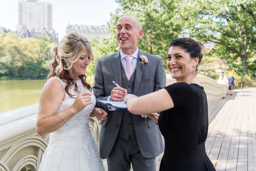 bride and groom signing wedding contract on bow bridge in central park with officiant Hope Mirlis