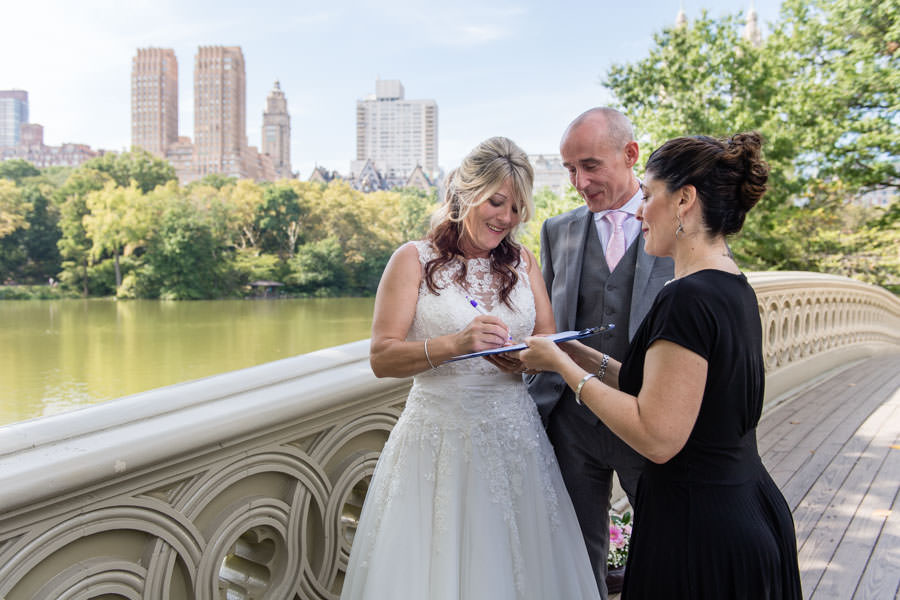 bride and groom signing marriage contract on bow bridge in central park after their elopement