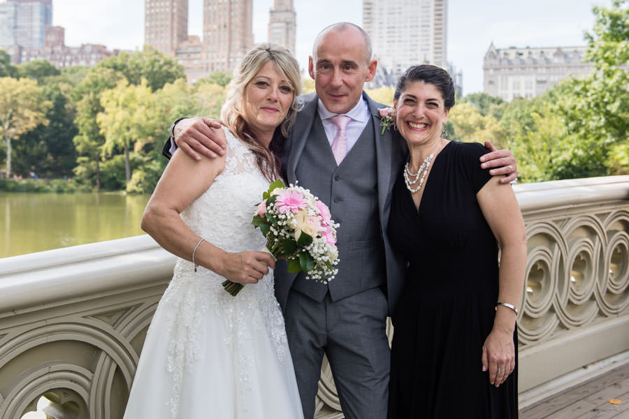Bride and groom pose for photo with officiant Hope Mirlis