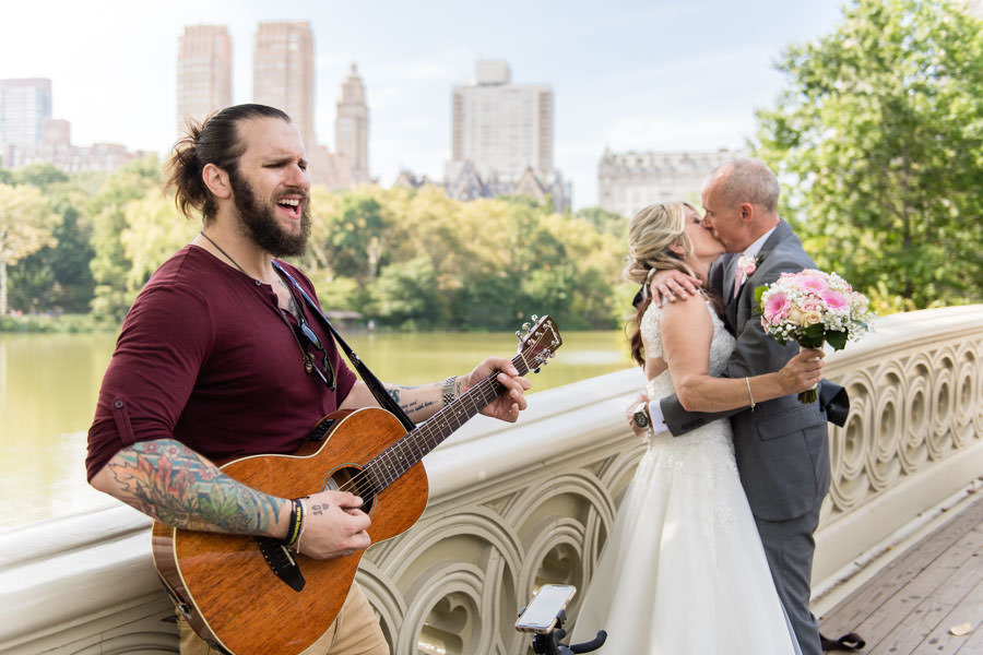 guitarist Brian Ripps performs on Bow Bridge in Central Park while bride and groom kiss in the background