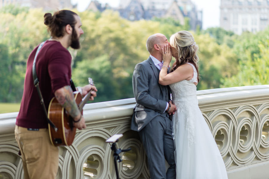 bride and groom kissing with guitarist Brian Ripps performing next to them on Bow Bridge in Central Park New York CIty