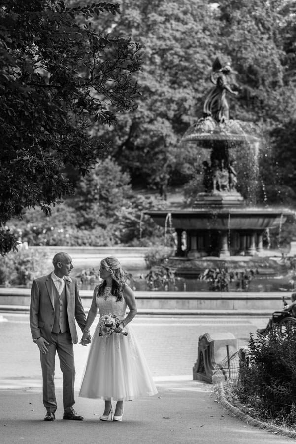 bride and groom walking with bethesda fountain in the background in central park new york city