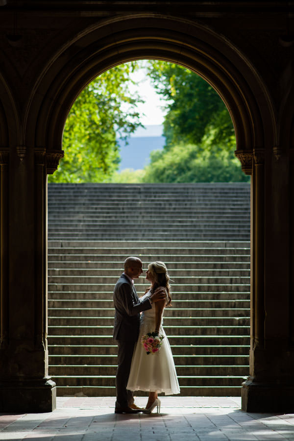 bride and groom pose for photo under bethesda terrace with dramatic lighting in central park new york city after their elopement