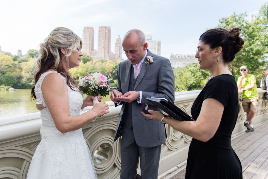 groom getting rings ready during elopement ceremony on bow bridge in central park