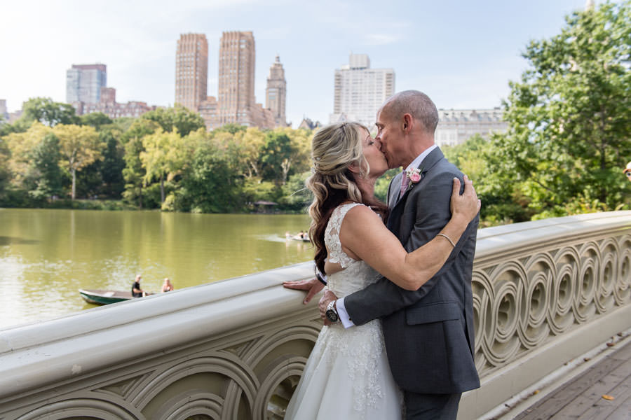 bride and groom kissing on bow bridge in central park