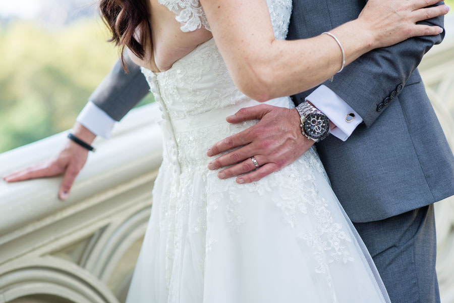 close up shot of groom holding bride's waist with watch visible