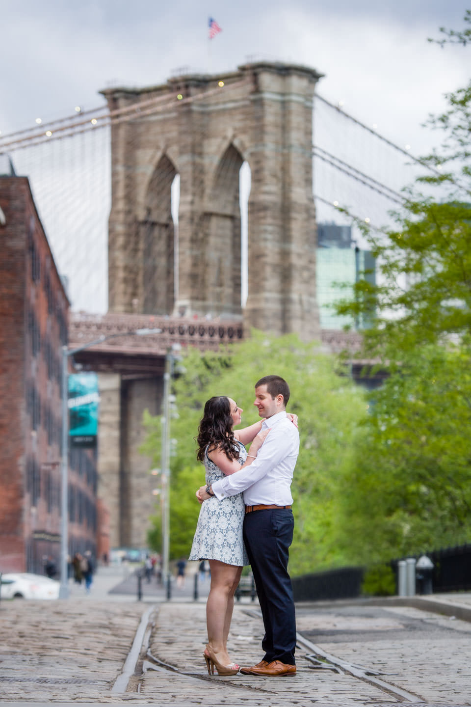 couple standing in front of brooklyn bridge in dumbo, brooklyn