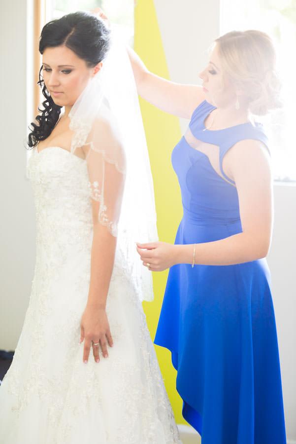 bride of honor helping bride with wedding veil