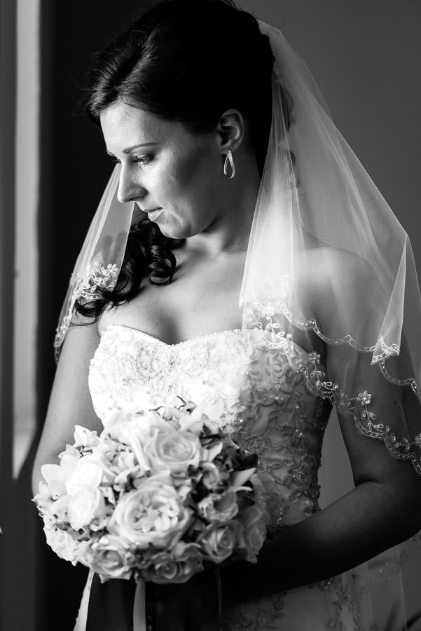 bride looking out window with beautiful light and bridal bouquet