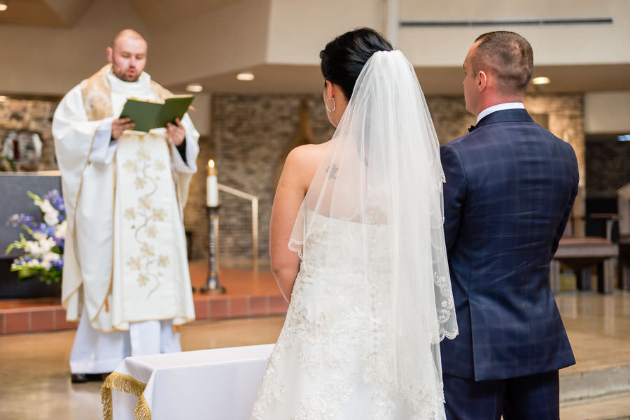 bride and groom in church during roman catholic ceremony