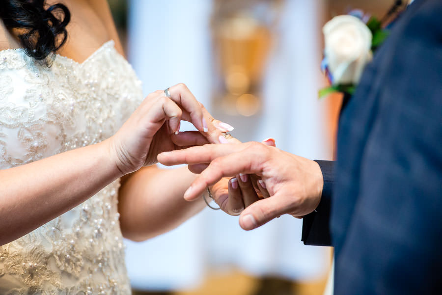 bride puts wedding band on groom's hand in church