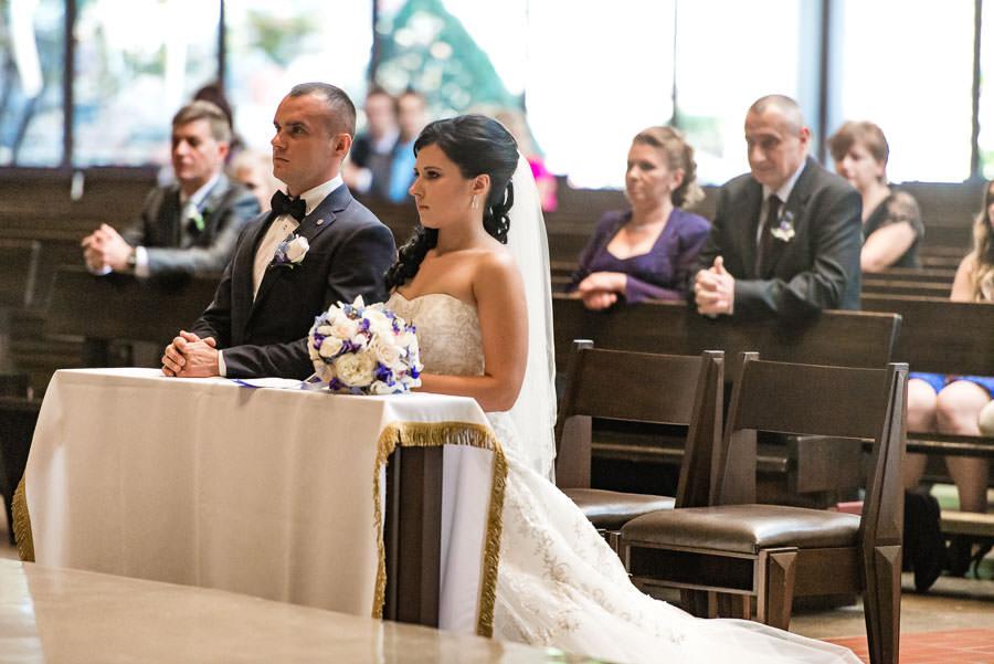 bride and groom kneeling in church during wedding