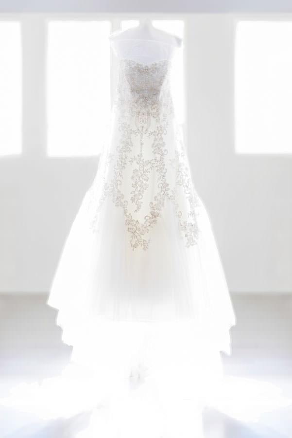 wedding dress hanging above window detail shot