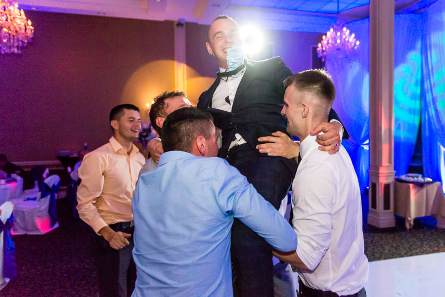 groom is picked up by group of his friends at wedding