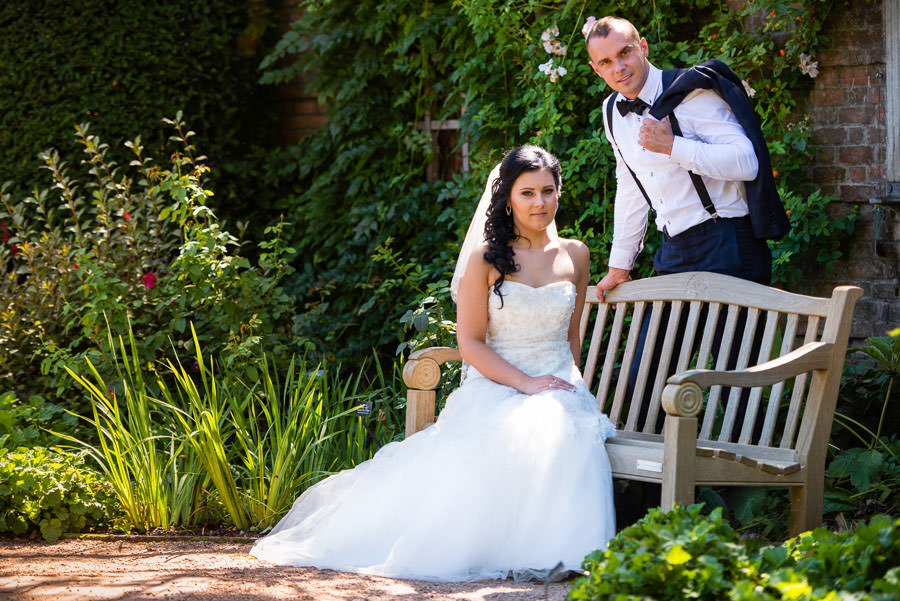 bride and groom pose on bench in botanic garden