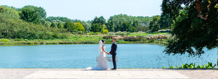 bride and groom standing in botanic garden with lake