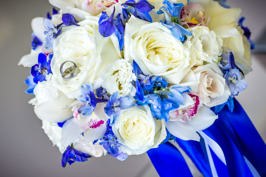 wedding rings on white roses with blue accents