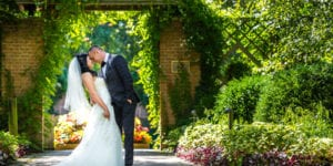 bride and groom hold each other in botanic garden with flowers in the summer