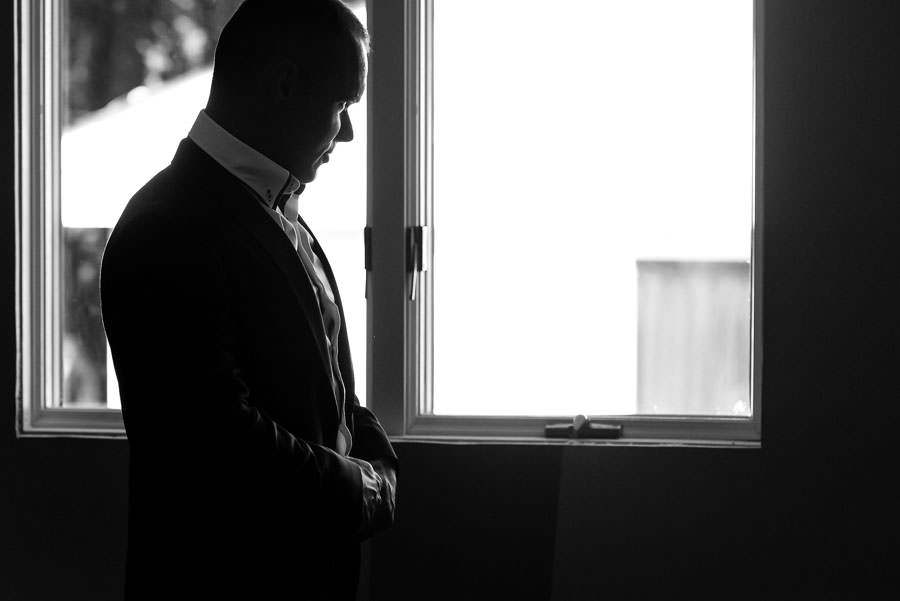 groom closing his jacket looking out window before wedding preparation