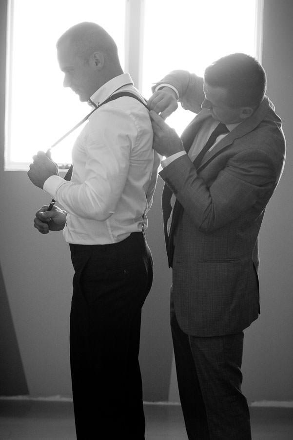 best man helping groom with suspenders
