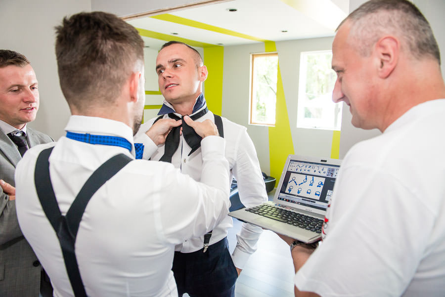 groomsmen helping groom tie a bowtie funny photo looking up instructions on google images