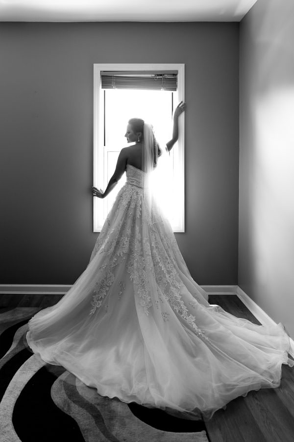 beautiful bride by window silhouette wearing david's bridal gown