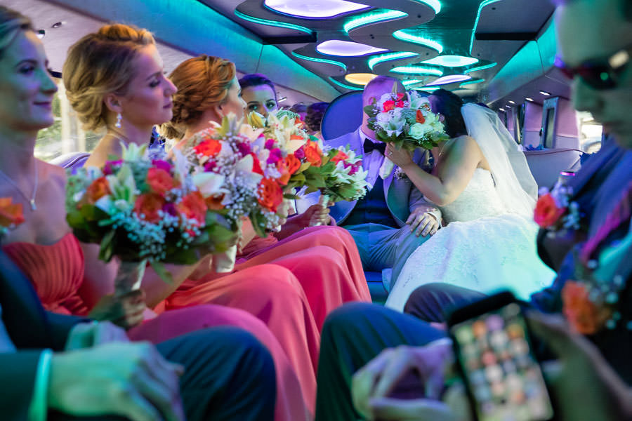 bride and groom covering faces with flowers when they kiss in the limo