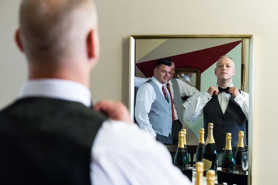 groom getting ready before wedding in mirror