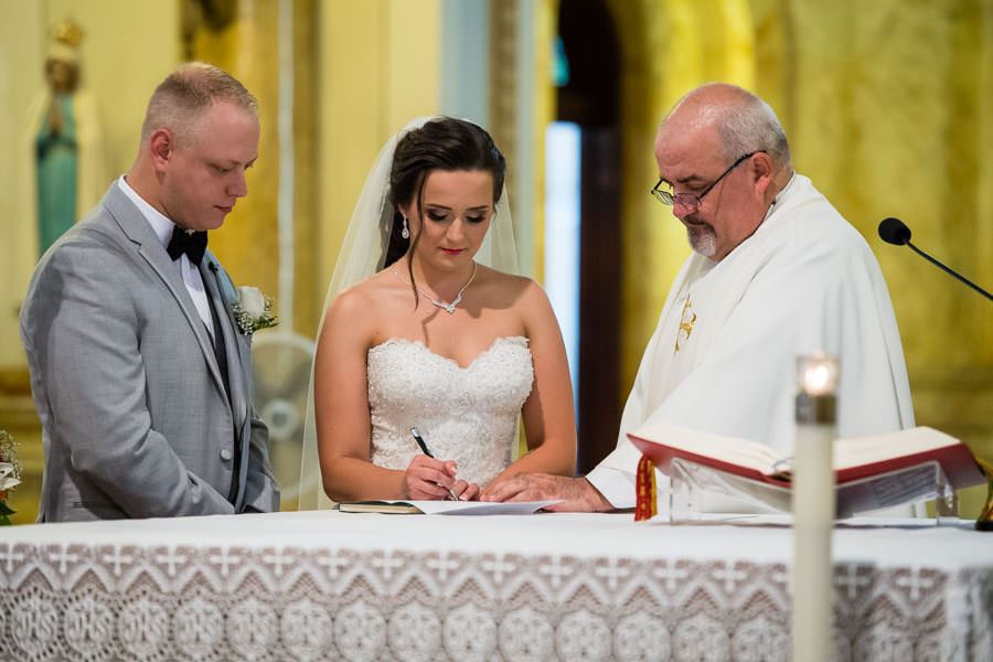 bride and groom signing marriage license in st aloysius church ridgewood ny