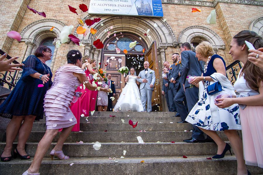 guests throw flower petals at bride and groom as they exit st aloysius church in ridgewood ny