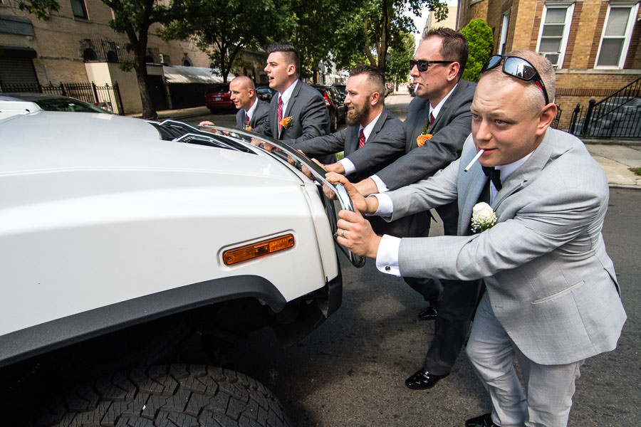 groom and groomsmen push limo after it broke down funny wedding photo