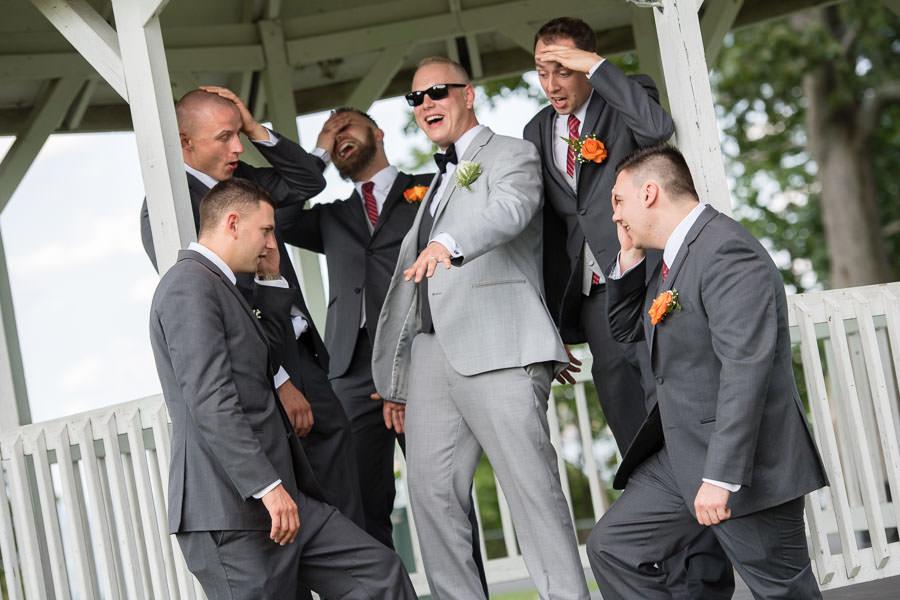 hilarious wedding day photo of groomsmen looking at grooms wedding ring