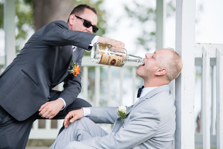 funny wedding day photo best man pouring vodka into grooms mouth