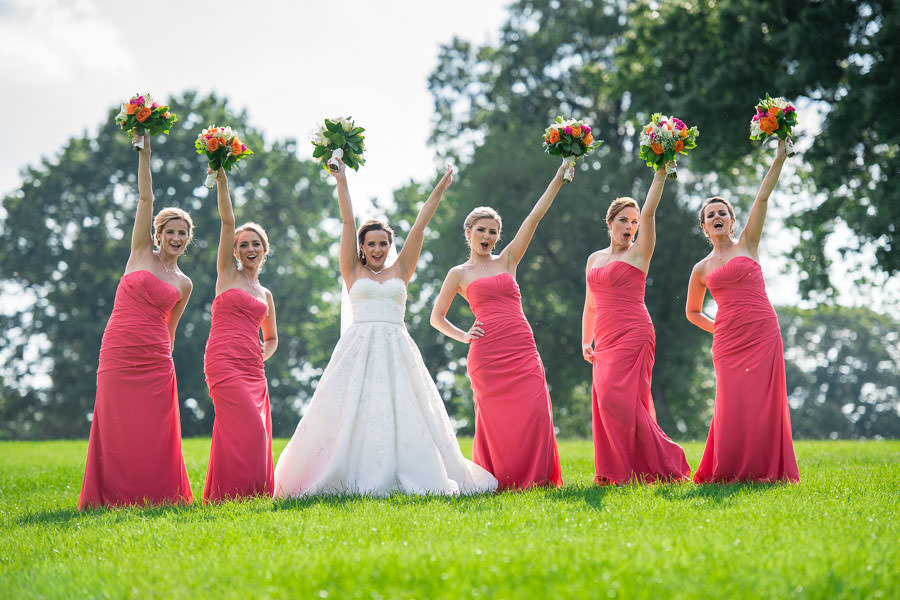 bridesmaids cheering and raising flowers on the grass together laughing in fort totten queens ny