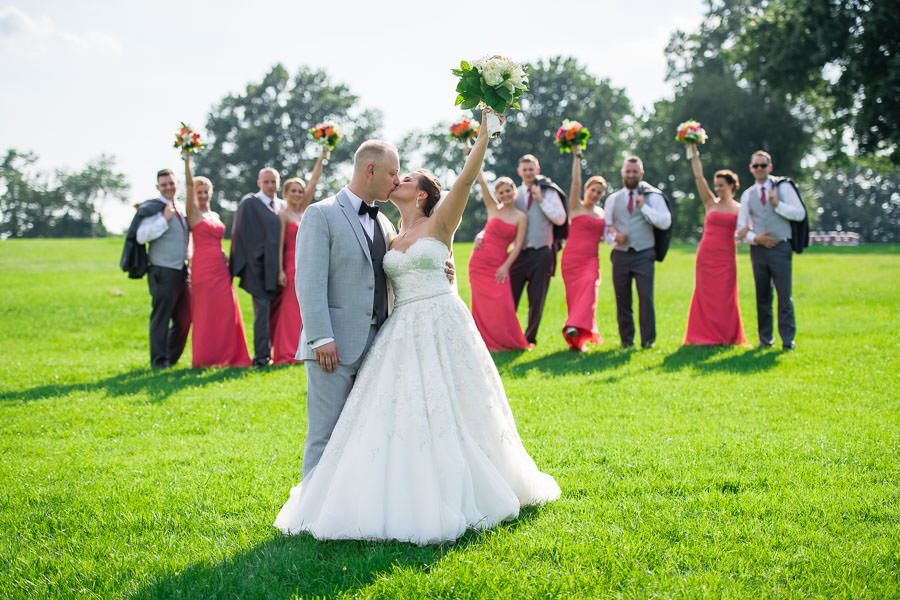bridesmaids cheering with bride and groom kissing and raising flowers on the grass together laughing in fort totten queens ny
