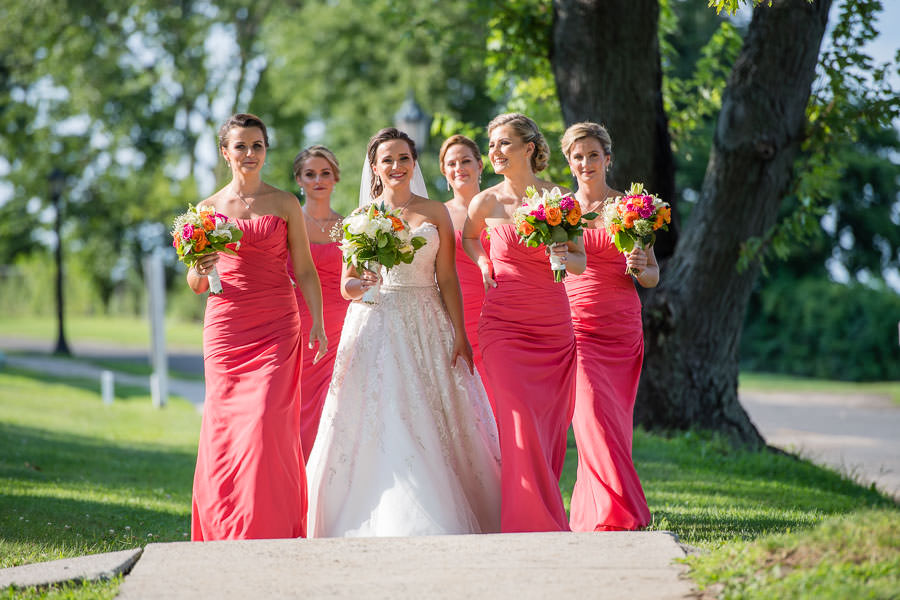 bridesmaids walk down path together laughing in fort totten park queens ny