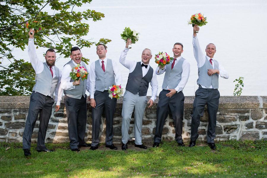 groom and groomsmen holding flowers in fort totten park