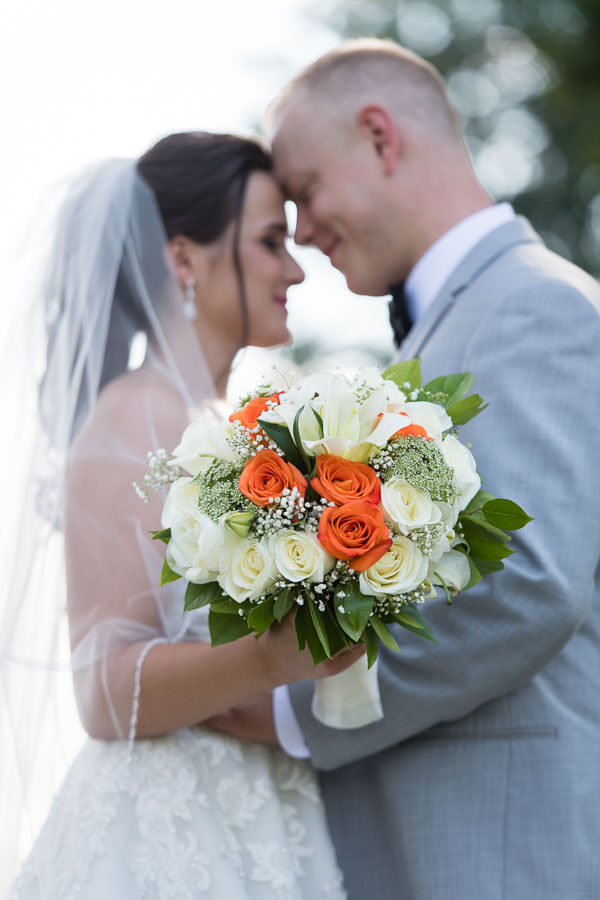 bride and groom posing together with bridal bouquet in focus artistic photo in fort totten park